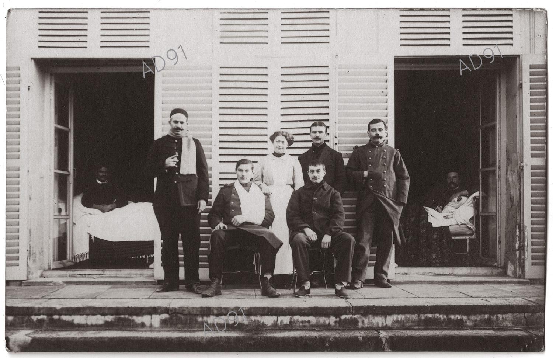 2 - Clémence Giraux avec les blessés de l'hôpital auxiliaire 191 de La Ferté-Alais installé dans la maison de Mme Dubreuil, 1914. (032NUM048/009)