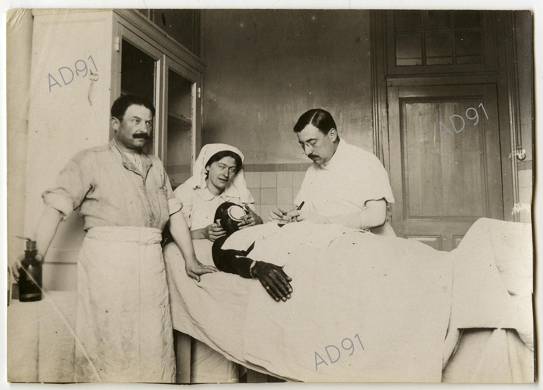 3 - Clémence Giraux avec les médecins opérant un blessé, ambulance 5/68 à Toul, 1915. (032NUM048/11)