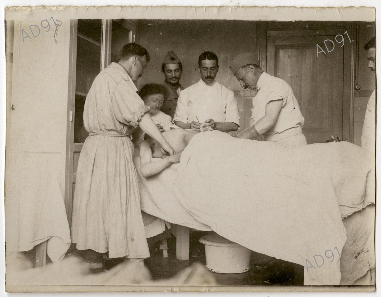 4 - Clémence Giraux avec les médecins opérant un blessé, ambulance 5/68 à Toul, 1915. (032NUM048/12)