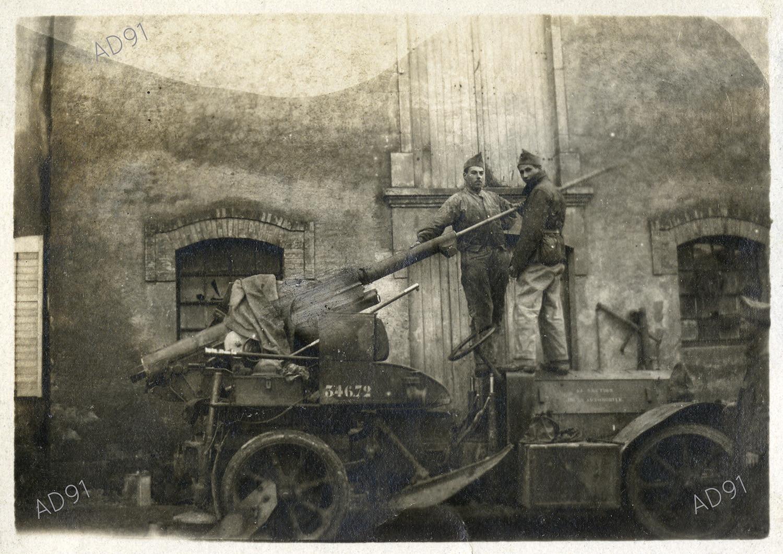 17 - Marcel Larcher debout sur une voiture auto-canon, photographie. (032NUM019/032)